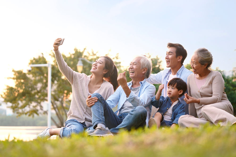 Three,Generation,Happy,Asian,Family,Sitting,On,Grass,Taking,A